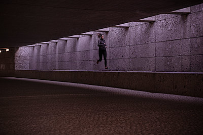 Female athlete running through pedestrian underpass - p300m2188251 by Studio 27