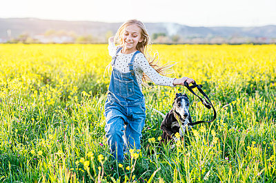 Smiling girl running with dog in agricultural field - p300m2282212 by Jose Luis CARRASCOSA