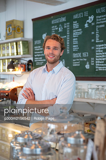 Young businessman in a cafe, with crossed arms behind counter - p300m2156542 by Robijn Page