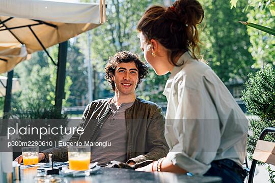 Smiling boyfriend sitting by girlfriend at sidewalk cafe - p300m2290610 by Eugenio Marongiu
