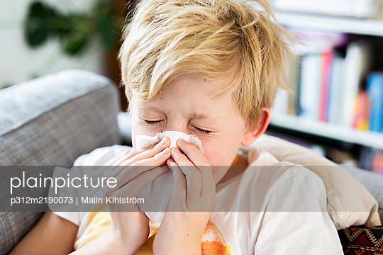Boy sneezing - p312m2190073 by Malin Kihlström