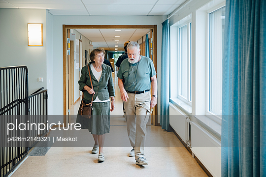 Full length of senior couple walking in alley at elderly nursing home - p426m2149321 by Maskot