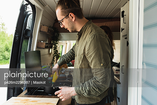 Side view of boyfriend preparing food with girlfriend in motor home - p426m2296387 by Maskot