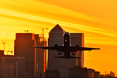 Airliner flying over London skyscrapers - p1048m2024238 by Mark Wagner