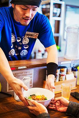 The ramen noodle shop. A chef delivering a bowl of ramen noodles to a customer.  - p1100m1185687 by Mint Images