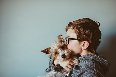 Side view of boy kissing Yorkshire Terrier against wall at home - p1166m1416305 by Cavan Images