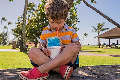 Boy eating slush while sitting on footpath at park - p1166m1542597 by Cavan Social