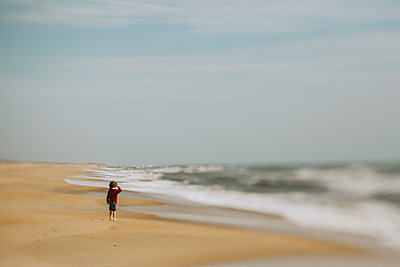 Side view of boy standing at shore against sky during sunny day - p1166m2034748 by Cavan Images
