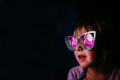 Girl looking at 4th of July fireworks with reflective glasses - p1166m2078368 by Cavan Images