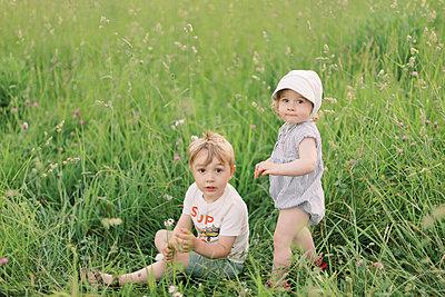 Siblings playing in a grassy meadow. - p1166m2153887 by Cavan Images