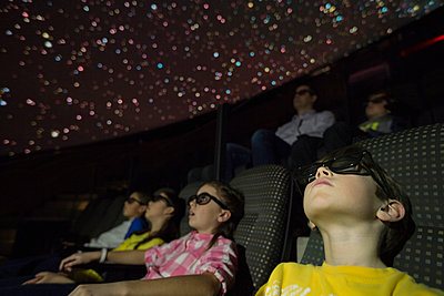 Students in 3D glasses enjoying planetarium show - p1192m1019866f by Hero Images
