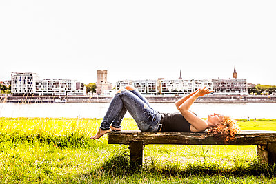 Germany, Cologne, redheaded young woman lying on bench taking selfie with cell phone - p300m2070636 by Jo Kirchherr