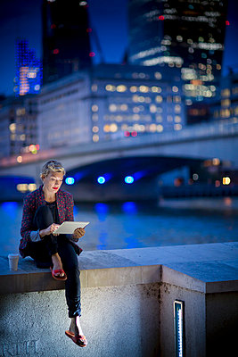Mature businesswoman on Thames waterfront using touchscreen on digital tablet at night, London, UK - p429m999634 by dotdotred