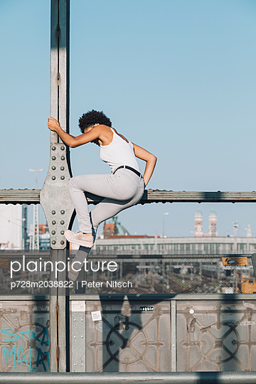 Weiblicher Teenager klettert auf einer Brücke - p728m2038822 von Peter Nitsch