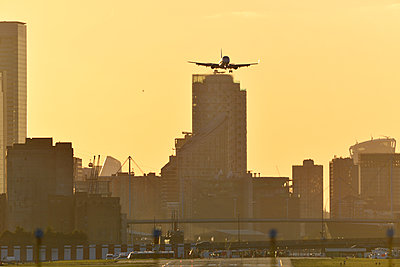 Airliner flying over London skyscrapers - p1048m2024247 by Mark Wagner
