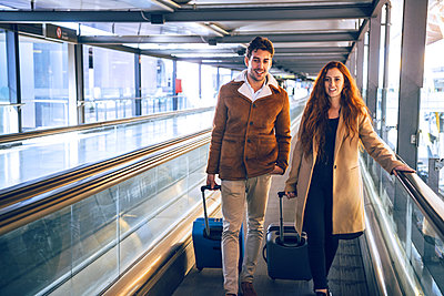 Business couple with luggage walking on moving walkway at airport - p300m2202606 by klublu