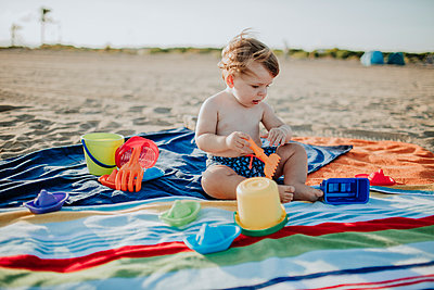 Baby boy playing with toys at beach during sunset - p300m2220941 by Gala Martínez López