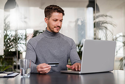Male entrepreneur paying online through credit card on laptop at office - p300m2264850 by Daniel Ingold