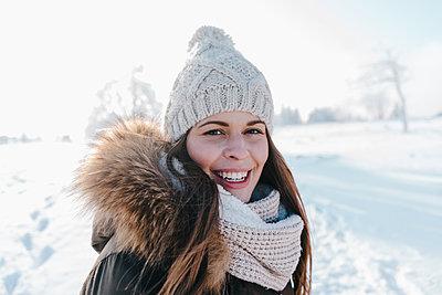Junge Frau in Winterkleidung in verschneiter Landschaft - p586m2005064 von Kniel Synnatzschke