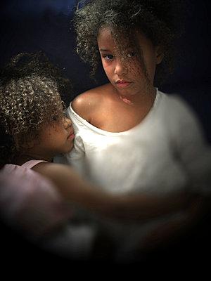 Schwestern mit Lockenkopf umarmen sich - p945m1480840 von aurelia frey