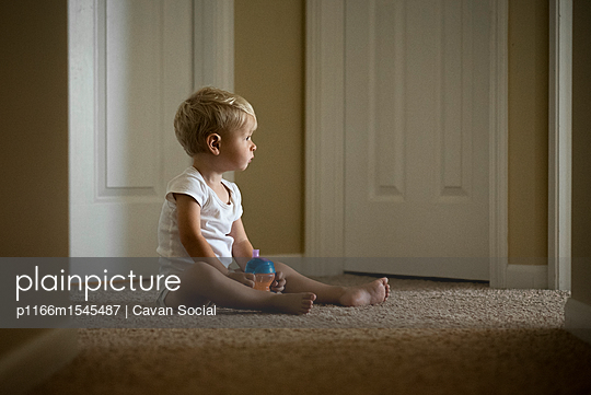 Cute boy with water bottle looking away while sitting on carpet at home - p1166m1545487 by Cavan Social