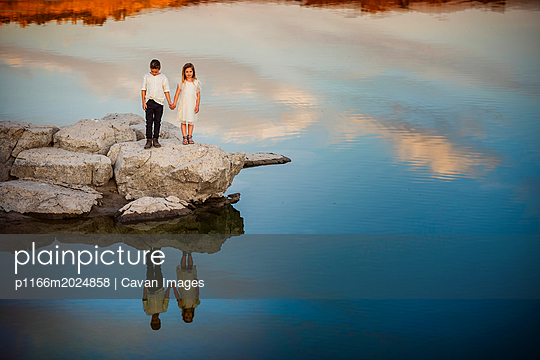 Full length of siblings holding hands while standing on rock by lake during sunset - p1166m2024858 by Cavan Images