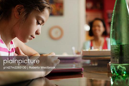 Girl using digital tablet - p1427m2283130 by Roberto Westbrook