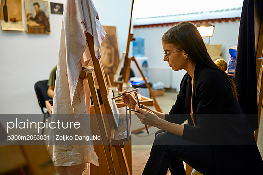 Student painting on easel in art class - p300m2063031 by Zeljko Dangubic