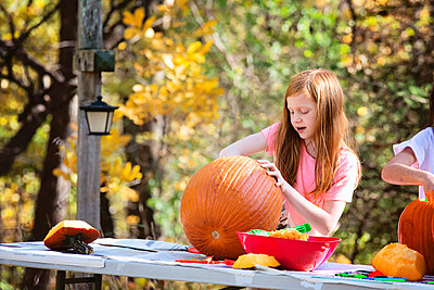 Young Red Haired Girl Carving a Pumpkin Outdoors - p1166m2147195 by Cavan Images