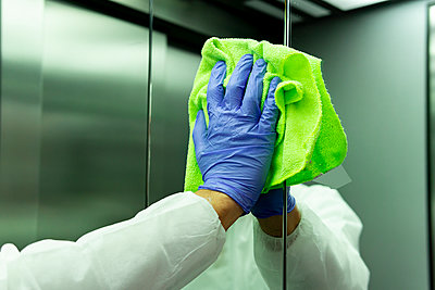coronavirus. Worker disinfecting hospital elevator to avoid contagion. - p1166m2171439 by Cavan Images