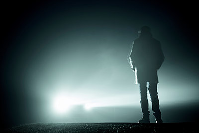 Rückansicht eines Mannes der im Licht der Scheinwerfer eines Autos im Nebel - p1312m2087539 von Axel Killian
