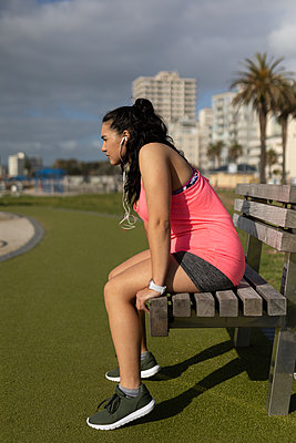 Female jogger sitting on bench at park - p1315m2062615 by Wavebreak