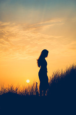 Silhouette of a woman at sunset - p1690m2281246 by Marie Carr