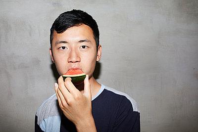 Young man bites into a piece of melon - p276m2115588 by plainpicture