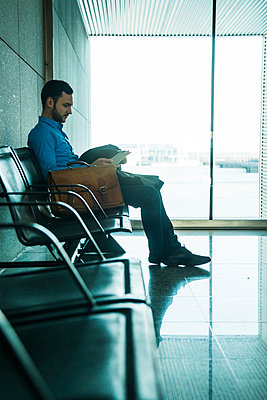 Young businessman with digital tablet at waiting area - p300m998351f by Uwe Umstätter
