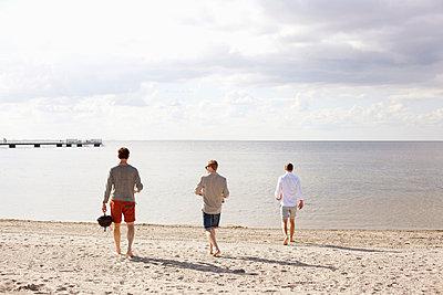 Rear view of men walking towards sea - p426m858046f by Astrakan