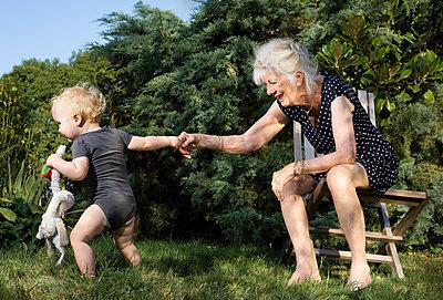 Grandmother and toddler in garden - p429m2019578 by Mischa Keijser