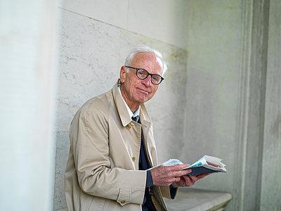 Senior man in raincoat reading newspaper, portrait, Copenhagen, Hovedstaden, Denmark - p429m2091735 by Soren Nielsen