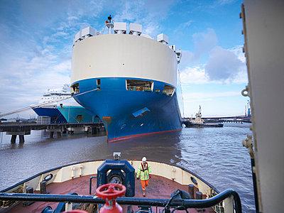 Worker standing on deck of tugboat - p429m747056f by Monty Rakusen