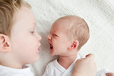 Infant boy crying at older brother - p429m817513 by Annie Engel photography