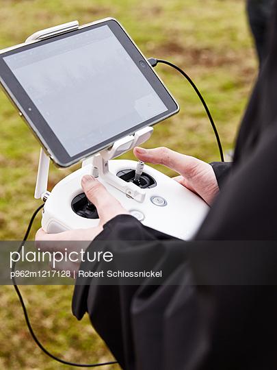 Person steuert eine Drohne - p962m1217128 von Robert Schlossnickel