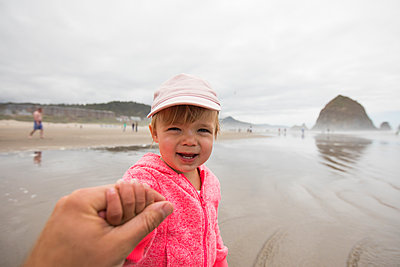 Portrait of young girl holding fathers hand at Cannon Beach. - p1166m2157212 by Cavan Images