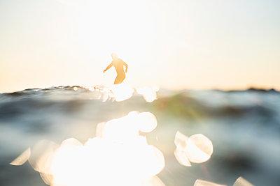 Backlit Man Surfing a wave during summer sunset - p1166m2279623 by Cavan Images