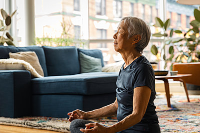 Asian senior woman meditating and relaxing at home in living room - p1166m2285600 by Cavan Images