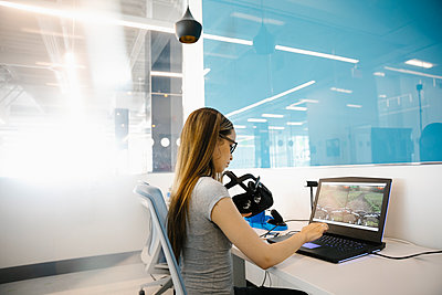 Student using laptop in VR room at university - p1192m2110179 by Hero Images