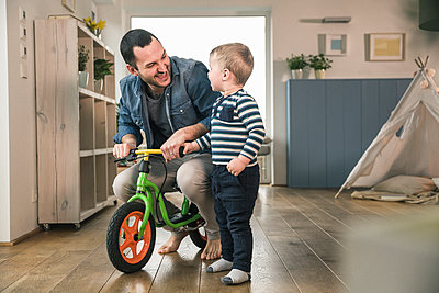 Father helping son riding with a balance bicycle at home - p300m2104492 by Uwe Umstätter