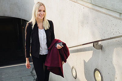 Blond businesswoman going out from metro station - p300m2154513 by Hernandez and Sorokina