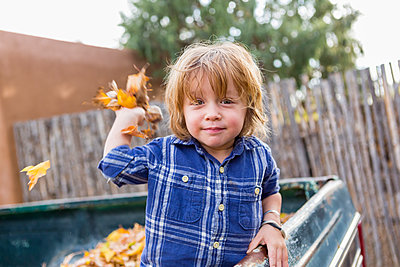 Caucasian boy playing in autumn leaves - p555m1410482 by Marc Romanelli