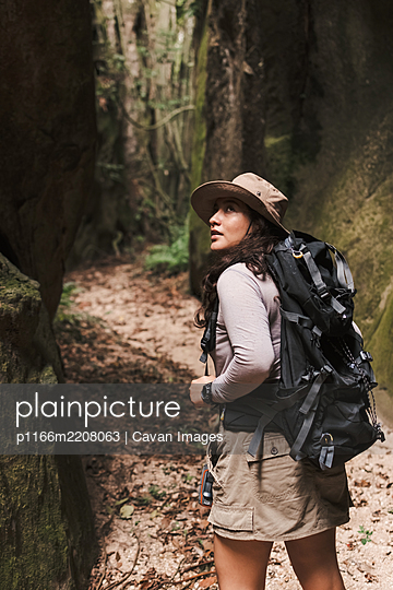 Young woman walking in a canyon with backpack looking back. - p1166m2208063 by Cavan Images