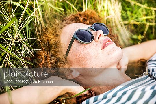 Young woman wearing sunglasses relaxing on a meadow - p300m2029071 by Jo Kirchherr